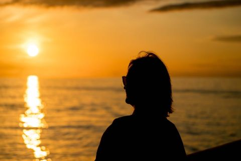 Lady silhouetted against an ocean sunset